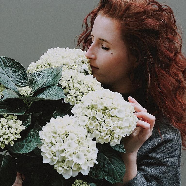 Обоняние. Девушка нюхает цветы